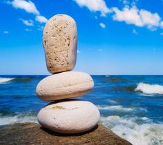 Three white pebbles against the background of the sea and sky